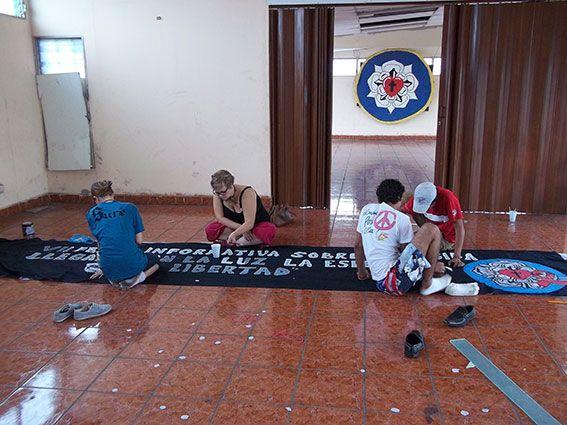 Freiwillige malt mit Jugendlichen vor Ort Plakate