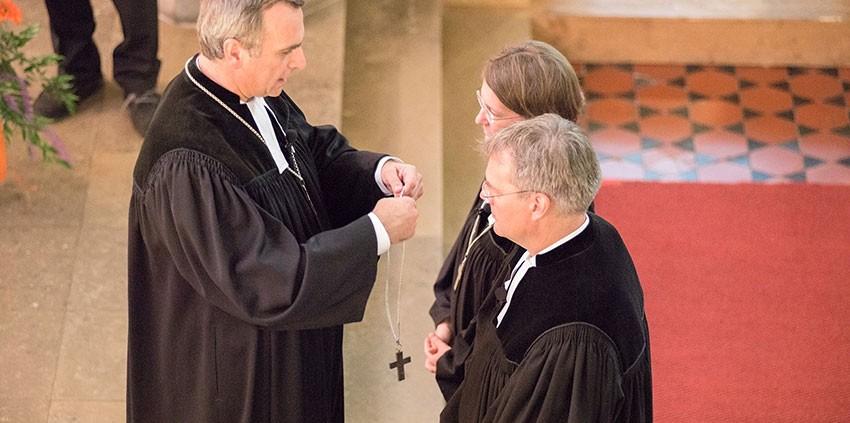 Oberkirchenrat Michael Martin legt den neuen Direktoren das Amtskreuz um. © MEW/Ermann