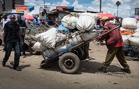 Männer ziehen einen vollbeladenen Wagen, Kenia
