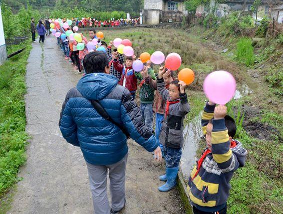 Kinder mit Luftballons vor der Schule – Das Gebäude wurde mit Hilfe der Amity Foundation wieder errichtet © MEW/Lachmann