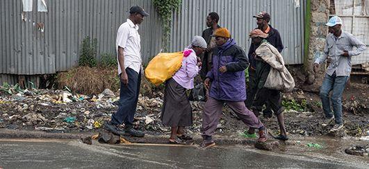 Menschen überqueren eine überschwemmte Straße, Kenia