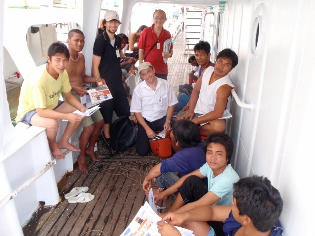 Die Mannschaft eines Fischerbootes versammelt an Deck